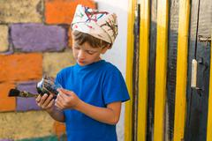 Boy performs painting works paint outdoors summer Stock Photos