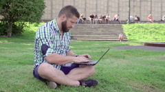 Young man writing on laptop, sitting on grass. Steadicam. Stock Footage