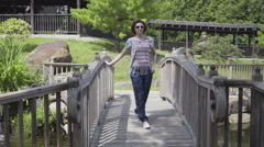 Young woman walking on suspended wooden bridge Stock Footage
