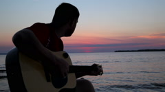 Boy plays on guitar at sunset Stock Footage