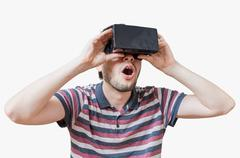 Man is wearing 3D virtual reality headset and is fascinated. Isolated on whit Stock Photos