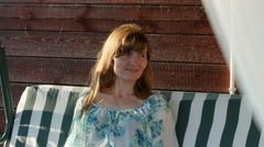 Portrait of beautiful woman in blue blouse sitting on a swing, Full HD shot Stock Footage