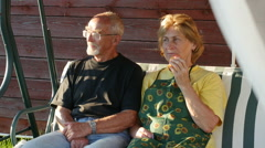 Elderly couple sitting on swing & talking in front of a country house, Full HD Stock Footage