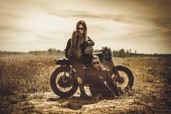 Stylish cafe racer couple on the vintage custom motorcycles in a field Stock Photos