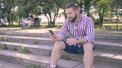 Young man browsing smartphone, sitting on stairs. Stock Footage