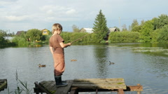 A little boy caught a small fish in the pond with ducks, Full HD footage Stock Footage