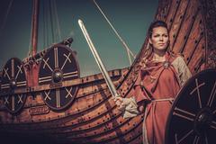 Viking woman with sword and shield standing near Drakkar on the seashore Stock Photos