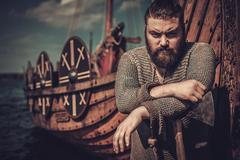 Viking warrior with axe standing near Drakkar on the seashore Stock Photos
