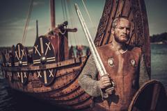Viking warrior with sword and shield standing near Drakkar on the seashore Stock Photos