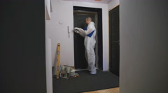 Worker in overalls, takes measurements of the doorway, he was a professional Stock Footage