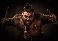 Screaming viking with axes in a traditional warrior clothes, posing on a dark Stock Photos