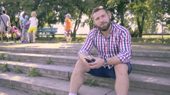 Young man browsing smartphone and telling to camera. Stock Footage