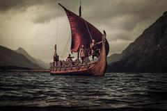 Vikings are floating on the sea on Drakkar with mountains on the Stock Photos