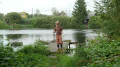 Little fisherman walking from the pond with a fishing rod & catch, Full HD shot Stock Footage