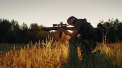 Armed men in camouflage. It takes aim at the optical sight. On the Sunset Stock Footage
