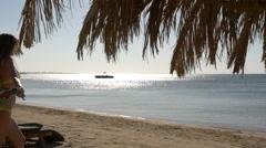 A slender girl runs on the beach with pareo. HD Stock Footage
