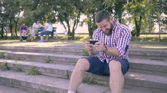 Young happy man playing games on smartphone in park. Stock Footage