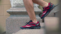 Man legs in running shoes walking down stairs. Closeup of legs in sport shoes Stock Footage