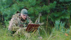 Armed men in camouflage sitting in the bush, uses a laptop Stock Footage