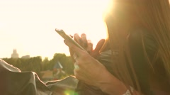 Brunette girl with dark nail polish tapping her mobile phone in sunny park Stock Footage