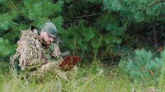 A man in military uniform sitting in the woods enjoying the laptop Stock Footage