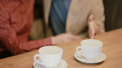 A view of empty coffee cups on the table and a couple holding hands Stock Footage