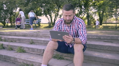 Young man browsing tablet, sitting on stairs. Slider shot. Stock Footage