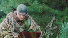 Portrait of military man sitting in the woods, dressed in camouflage. It uses Stock Footage