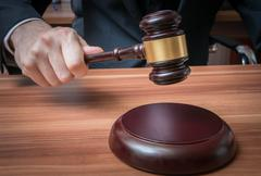 Auctioneer or judge is hitting with wooden gavel. Stock Photos