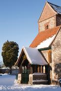 Old English church covered in snow in winter Stock Photos