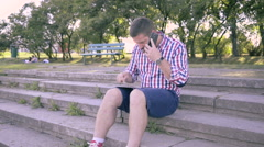 Young man talking by smartphone and browsing tablet. Stock Footage