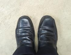 Close up of businessman feet in black boots Stock Photos