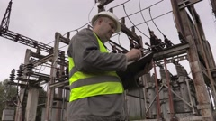 Electrician writing in electrical substation Stock Footage