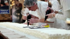 Confectioner prepares cream cake White delicious large freshly baked cake Stock Footage