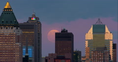 Full moon rises behind New York City skyscrapers on a clear night. Stock Footage