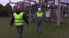 Electricians talking in electrical substation Stock Footage