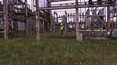 Electrician talking on phone and walking in electrical substation Stock Footage