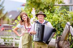 Couple in traditional bavarian clothes with accordion, green gar Stock Photos