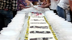 Cutting a large cake, workers, confectioners spread a huge cake on plastic Stock Footage