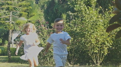 Happy children playing catch-up game. Slow motion Stock Footage