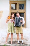 Couple in traditional bavarian clothes with beer and accordion Stock Photos