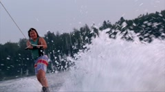 Wakeboarder woman riding waves on lake water, beautiful purple Stock Footage