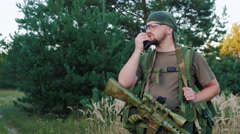 Man in camouflage with guns. Speaking on the radio Stock Footage