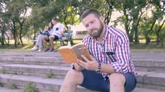 Young man reading book, sitting on stairs. Stock Footage