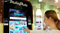 Instafoto the machine for printing, the mall girl chooses a photo on the device Stock Footage