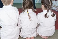 Group of children in kimono sitting on tatami on martial arts training seminar Stock Photos