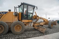 Grader leveling gravel on construction site Stock Photos