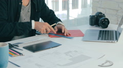 Unrecognizable creative designer working in modern office. Cutting sheets Stock Footage