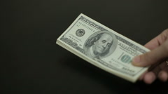 A large stack of hundred dollar bills on a table gradually blows away Stock Footage