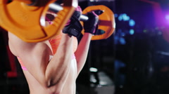 Athletic woman trains muscles of the hands with a barbell. Female bodybuilding Stock Footage